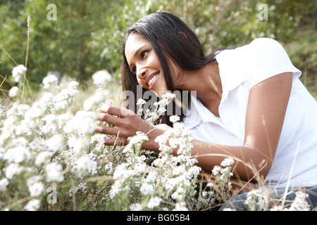 Woman lying in field of white flowers - Stock Photo