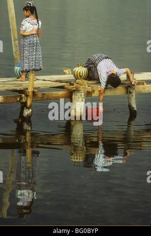 Women fetch water from Lake Atitlan near Santiago Atitlan, Guatemala - Stock Photo