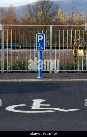 post with disabled parking sign in front of a parking bay in a car park in the uk ireland - Stock Photo