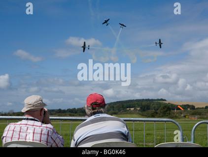 Two men watching four plane aerobatic display. Shoreham Airport, Sussex, England - Stock Photo