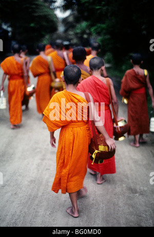A group of monks in Luang Prabang, Laos on their way to collect alms This is a daily ritual that starts at 6 in - Stock Photo