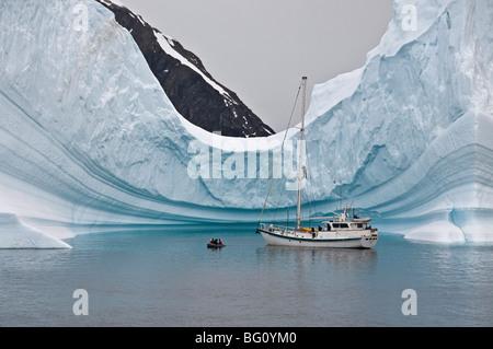 Sailing yacht and iceberg, Errera Channel, Antarctic Peninsula, Antarctica, Polar Regions - Stock Photo