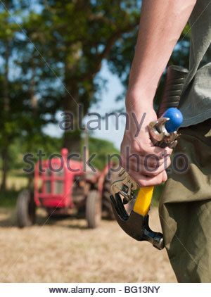 man holding tools by tractor - Stock Photo