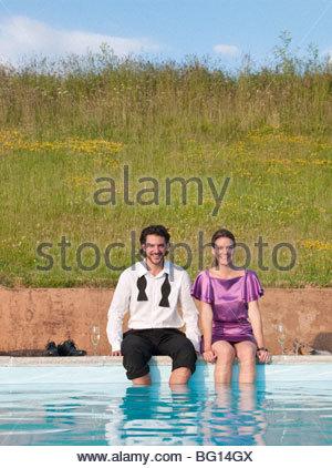 couple sat feet in swimming pool - Stock Photo