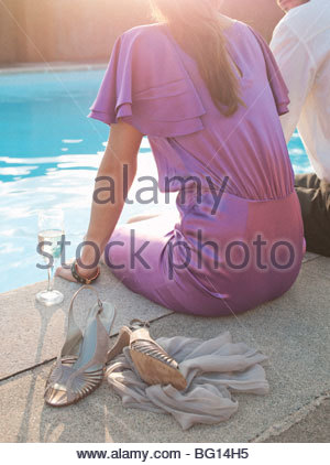 couple sat by swimming pool, - Stock Photo