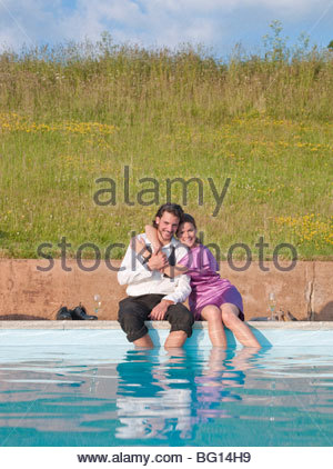 couple sat by swimming pool,embraced - Stock Photo