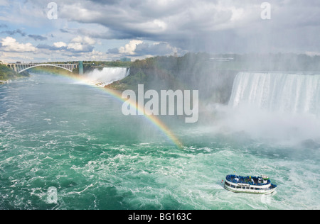 Maid of the Mist tour excursion boat under the Horseshoe Falls waterfall with rainbow at Niagara Falls, Ontario, - Stock Photo