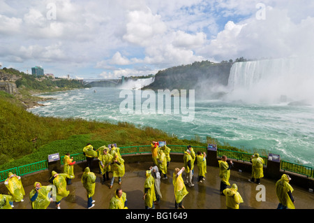 Tourists in yellow raincoats, Horseshoe Falls waterfall whilst on Journey under the Falls tour, Niagara Falls, Ontario, - Stock Photo
