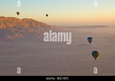Hot air balloons flying over desert at dawn on the West bank of the river Nile near Luxor, Egypt, North Africa - Stock Photo
