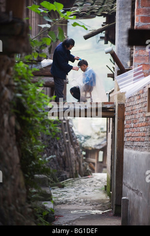 An outdoor barber cutting a boy's hair in Langde village, Guizhou Province, China, Asia - Stock Photo