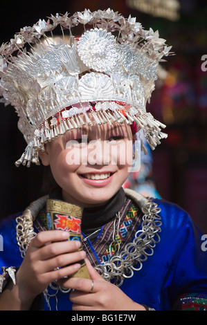 Girl welcoming visitors with a horn of rice wine at a Miao New Year festival in Xijiang, Guizhou Province, China - Stock Photo