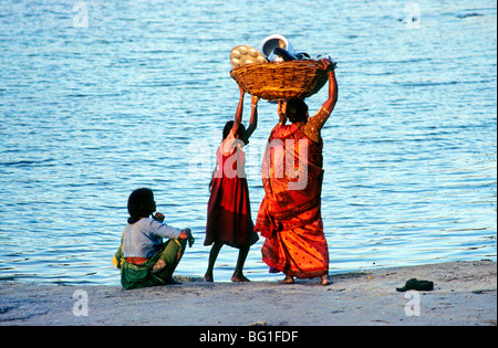 A mother and daughter carry dishes and utensils to the Tungabhadra River in Hampi, India for washing - Stock Photo