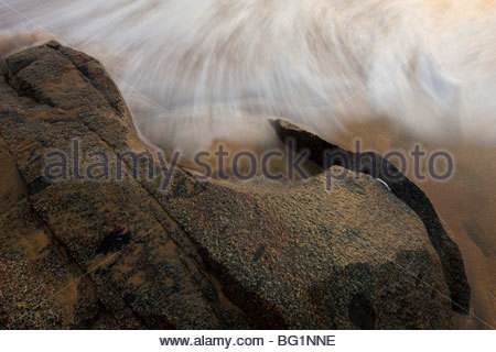 Pacific Ocean waves crash up against the rocky shoreline on a beach in Sayulita, Mexico. - Stock Photo
