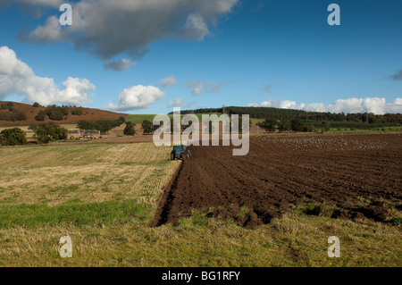 Farmer ploughing field of stubble in. Autumn. - Stock Photo
