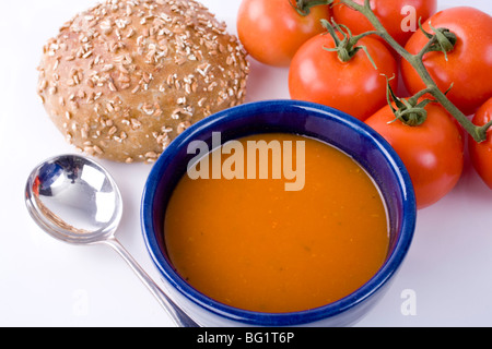 Roast pepper and tomato soup with bread roll and tomatoes on vine. - Stock Photo