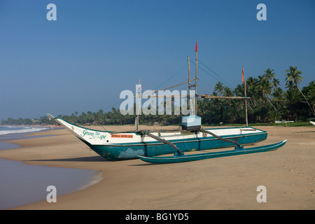 Outrigger fishing boats on Hikkaduwa beach, Sri Lanka - Stock Photo