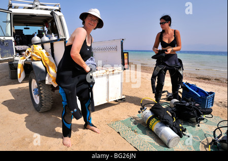 Two woman scuba divers prepare on beach for a shore dive, Nuweiba, 'Red Sea', Egypt - Stock Photo