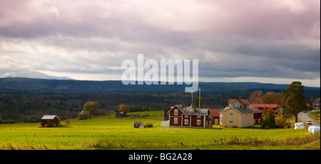 View over traditional farm with swedish flags and forest and fjells with first snow Jämtland Sweden in autumn with - Stock Photo