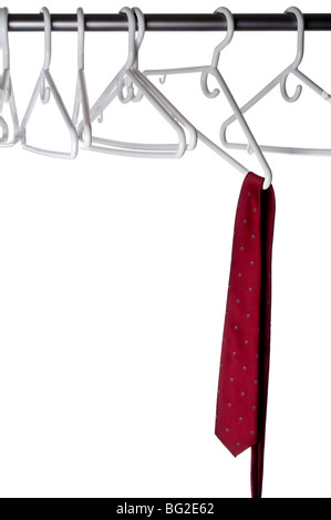 A burgundy tie on a hanger attached to a closet pole - Stock Photo