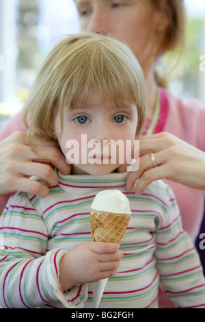 Beautiful toddler blond little girl eating ice cream, mother taking care - Stock Photo