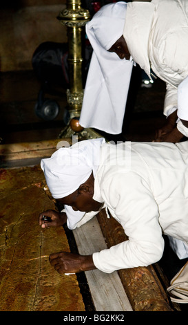 African nuns pray in front of the Stone of Anointing, also known as the The Stone of Unction in the church of the - Stock Photo