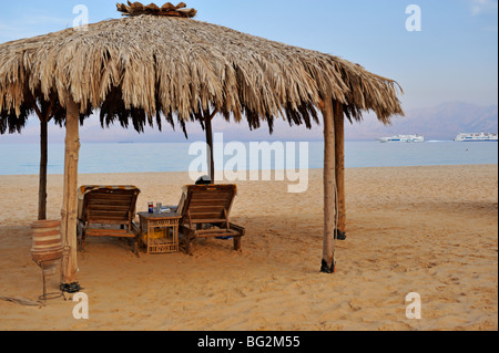 Relaxation on beach by sea under thatched sunshade, Nuweiba, 'Red Sea', Sinai, Egypt - Stock Photo