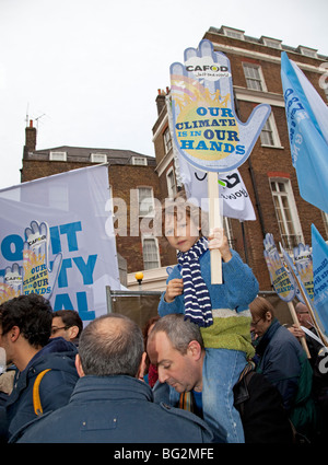 Young boy sitting on fathers shoulders with Cafod Our Climate in our Hands placard The Wave Climate Change March - Stock Photo