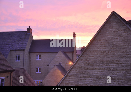 Sunset over roofs of houses in new build development in Witney UK - Stock Photo