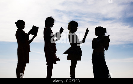 Silhouette of Indian girls reading books standing in a line - Stock Photo