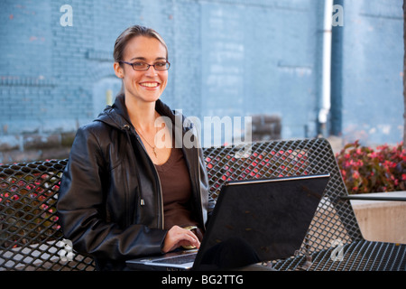 Smiling woman sitting on a parkbench with a notebook computer. - Stock Photo