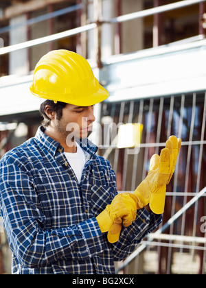 construction worker putting on protective gloves - Stock Photo