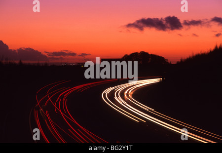 headlight trails of traffic travelling on the A1/M1 motorway at sunset near leeds uk - Stock Photo