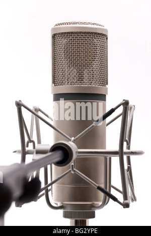 A large diaphragm microphone on boom attached with a shockmount against a white background - Stock Photo