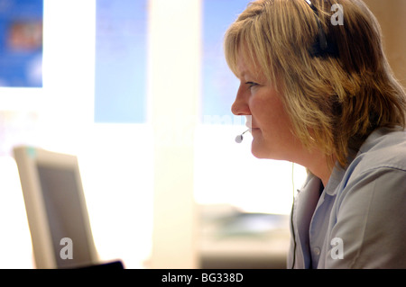 Royalty free photograph of customer support operator helping client on telephone in UK London offices. - Stock Photo