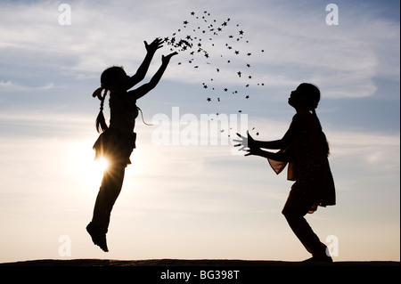 Silhouette of two young Indian girls jumping, throwing and catching stars. India - Stock Photo