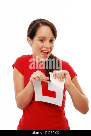 Young girl learner driver ripping up an l plate - Stock Photo