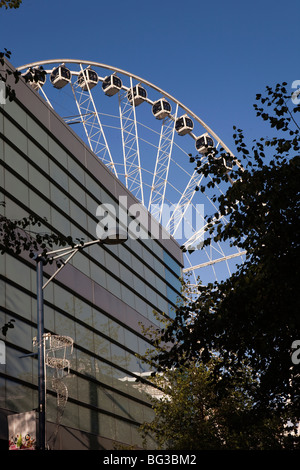 UK, England, Manchester, Cathedral Street, Manchester Wheel towering over buildings - Stock Photo