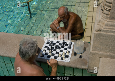 Two men playing chess in thermal pool, Szechenyi Thermal Bath, Budapest, Hungary - Stock Photo