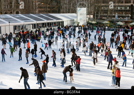 happy multicultural crowd of Sunday skaters have fun on the ice of the Bryant Park free skating pond in Manhattan - Stock Photo