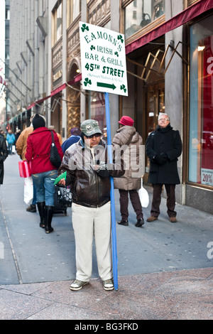 blind man among shoppers on Fifth Avenue in New York City patiently holding the pole of sign directing people to - Stock Photo