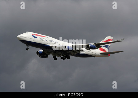 British Airways Boeing 747-400 long haul commercial passenger jet flying on approach in a dark cloudy sky - Stock Photo