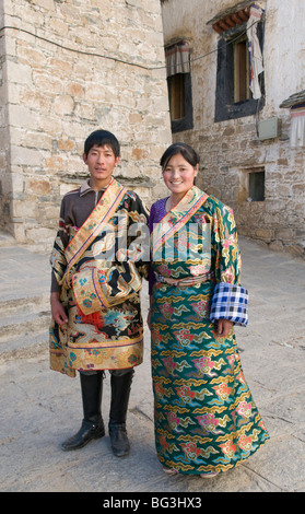 A young Tibetan couple dressed up in traditional Tibetan dress visit Drepung Monastery in Lhasa Tibet - Stock Photo