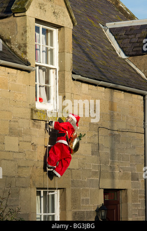 Waterproof and snowproof model Santa climbs rope ladder to the bedroom window - Christmas decoration seen in Kelso - Stock Photo