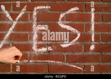 The word 'yes' written on a red rick wall in chalk. - Stock Photo