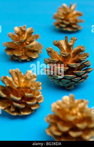 Golden pine cones looking like Christmas trees on blue background - Stock Photo