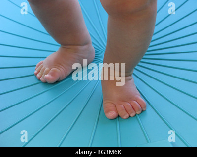 Legs and feet of an infant learning to walk in a blue environment - Stock Photo