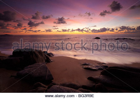 High cirrus clouds high over a beach near Sayulita, Mexico, are turned red and orange after sunset. - Stock Photo