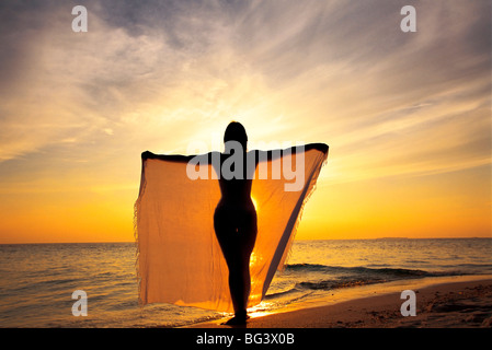 Woman on a beach at sunset, Maldives, Indian Ocean, Asia - Stock Photo