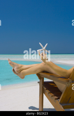 Woman holding seastar on the beach, Maldives, Indian Ocean, Asia - Stock Photo