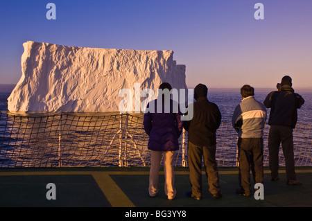 Passengers viewing iceberg in the Gerlache Strait, Antarctica, Polar Regions - Stock Photo